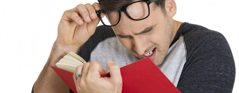 Closeup portrait of young nerdy guy with big black eye glasses trying to read book but having difficulties seeing text because of vision problems. Negative emotion facial expression feelings