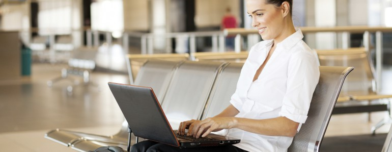 young woman using laptop computer at airport